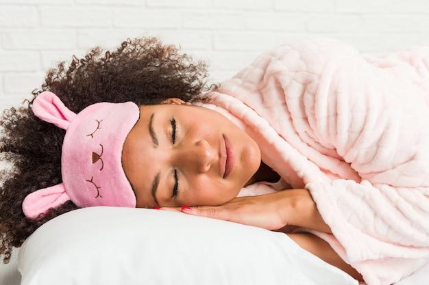 Jeune femme afro-américaine dormant avec un oreiller sur le lit