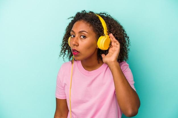 Jeune femme afro-américaine écoutant de la musique isolée sur fond bleu essayant d'écouter un potin.