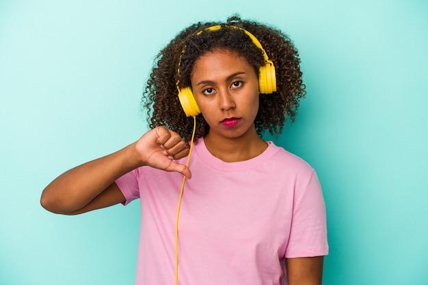 Jeune femme afro-américaine écoutant de la musique isolée sur fond bleu montrant un geste d'aversion, les pouces vers le bas. notion de désaccord.