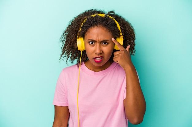 Jeune femme afro-américaine écoutant de la musique isolée sur fond bleu montrant un geste de déception avec l'index.