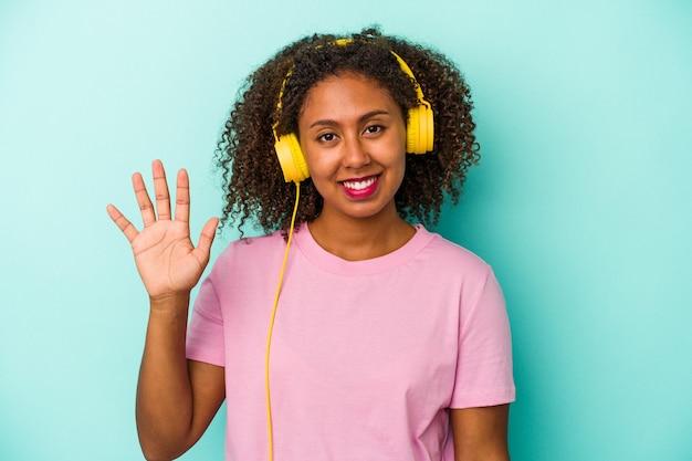 Jeune femme afro-américaine écoutant de la musique isolée sur fond bleu souriant joyeux montrant le numéro cinq avec les doigts.