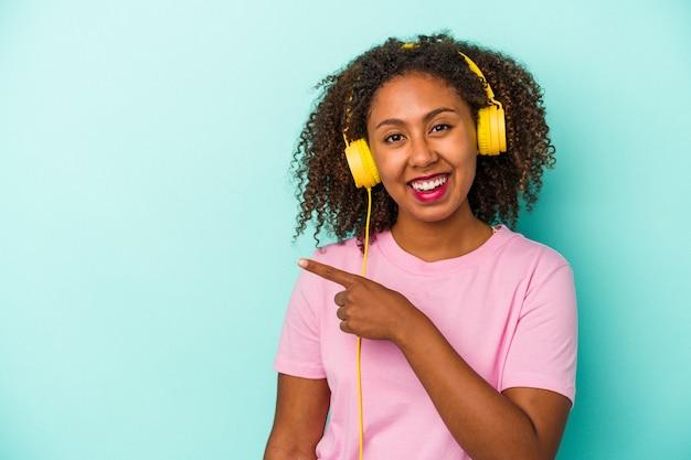 Jeune femme afro-américaine écoutant de la musique isolée sur fond bleu souriant et pointant de côté, montrant quelque chose dans un espace vide.