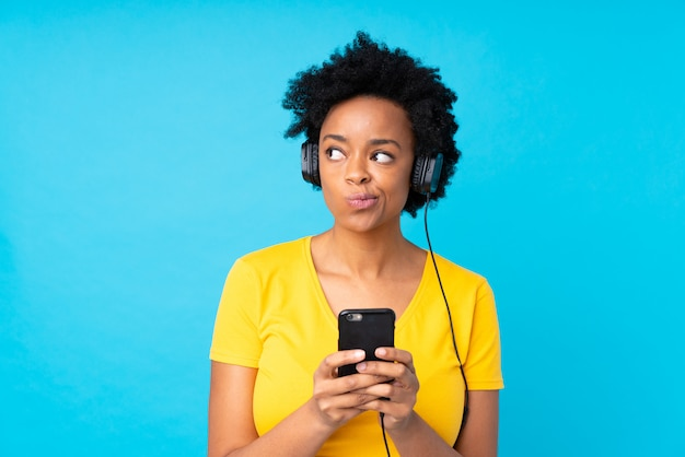 Jeune femme afro-américaine écoute de la musique avec un téléphone portable sur un mur bleu isolé