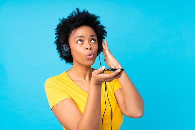 Jeune femme afro-américaine écoute de la musique avec un téléphone portable