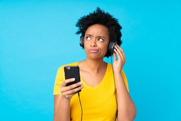 Jeune femme afro-américaine, écouter de la musique avec un mobile sur un mur bleu isolé