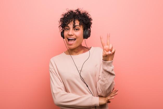 Jeune femme afro-américaine, écouter de la musique montrant le numéro deux avec les doigts.