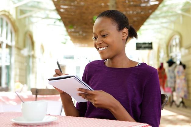Jeune femme afro-américaine, écrivant des notes au café