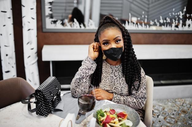 Jeune femme afro-américaine élégante, portant un masque noir, assis au restaurant, appréciant une nourriture saine avec du vin.