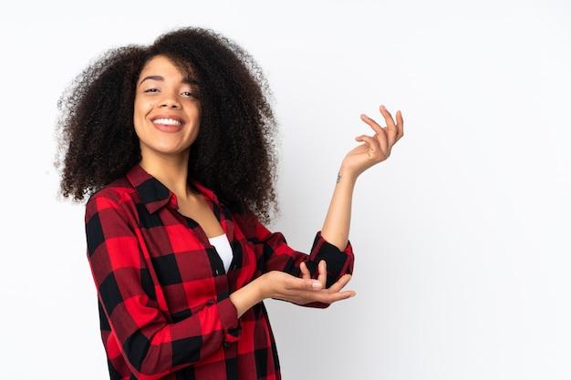 Jeune femme afro-américaine étendant les mains sur le côté pour inviter à venir