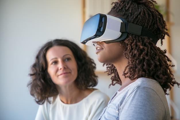 Jeune femme afro-américaine excitée dans le casque de réalité virtuelle