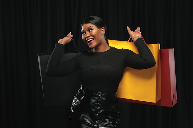 Jeune femme afro-américaine, faire du shopping avec des packs colorés sur fond noir