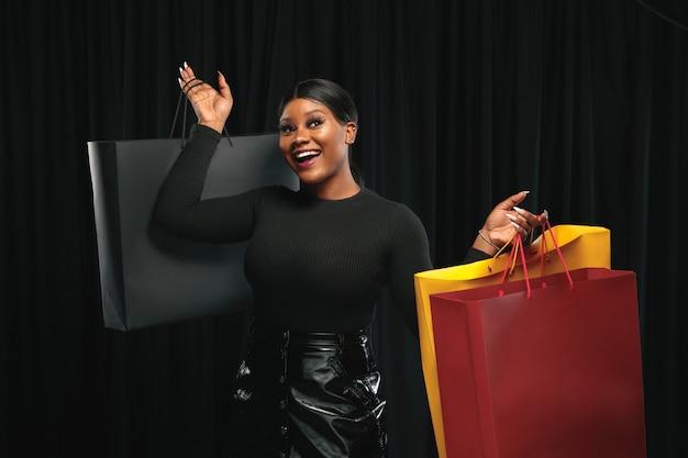 Jeune femme afro-américaine faisant du shopping avec des packs colorés sur un mur noir.