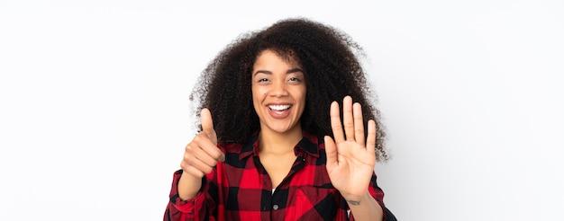 Jeune femme afro-américaine sur fond isolé comptant six avec les doigts