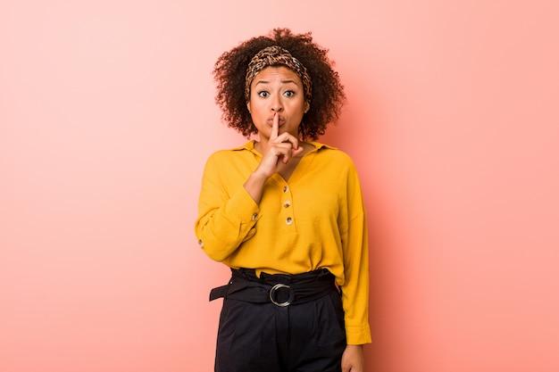 Jeune femme afro-américaine sur un fond rose gardant un secret ou demandant le silence.