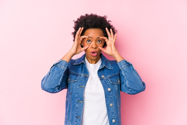 Jeune femme afro-américaine sur un fond rose isolé en gardant les yeux ouverts pour trouver une opportunité de succès.