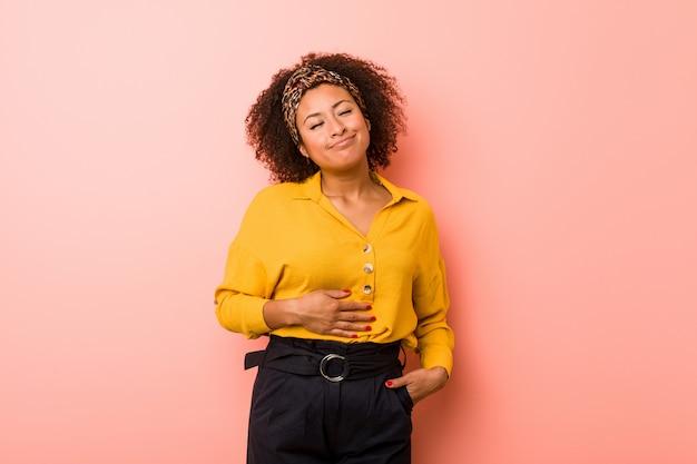 Jeune femme afro-américaine sur un fond rose touche le ventre, sourit doucement, concept de manger et de satisfaction.