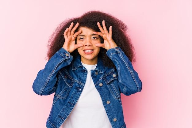 Jeune femme afro-américaine en gardant les yeux ouverts pour trouver une opportunité de réussite.