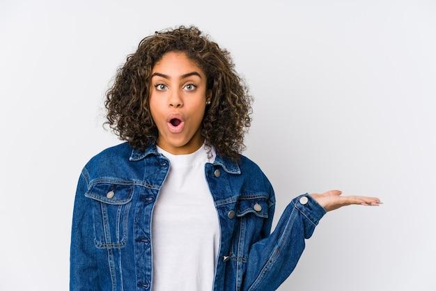 Jeune femme afro-américaine impressionnée tenant un espace de copie sur la paume.