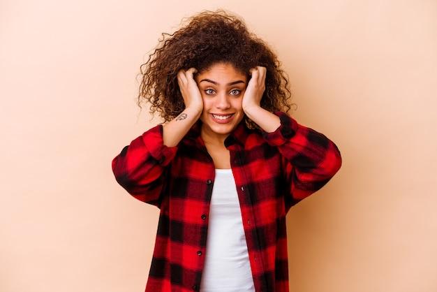 Jeune femme afro-américaine isolée sur beige pleurer, mécontente de quelque chose, l'agonie et le concept de confusion.