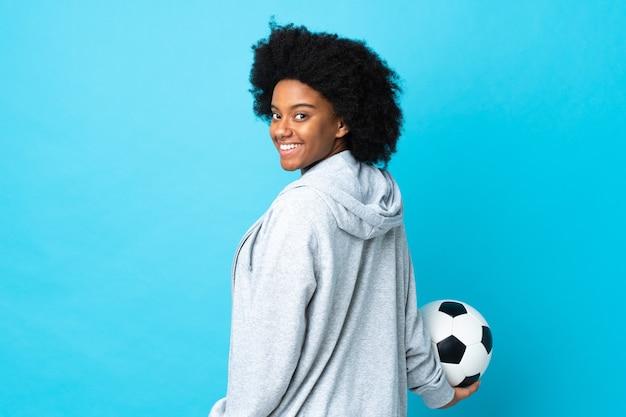 Jeune femme afro-américaine isolée sur bleu avec ballon de foot