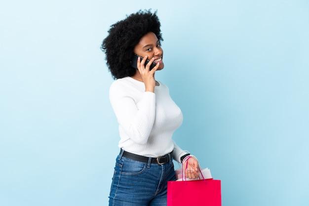 Jeune femme afro-américaine isolée sur bleu tenant des sacs à provisions et appeler un ami avec son téléphone portable