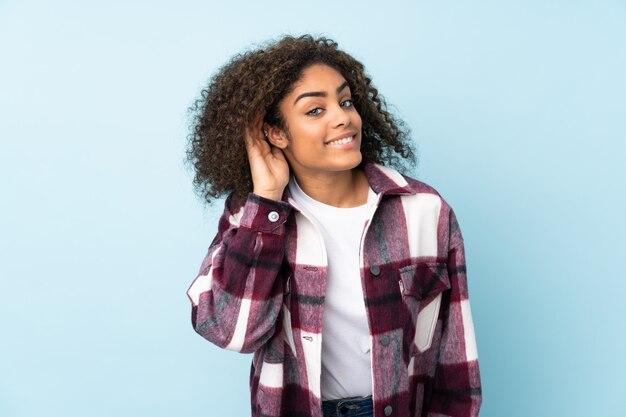 Jeune femme afro-américaine isolée sur un espace bleu en écoutant quelque chose en mettant la main sur l'oreille