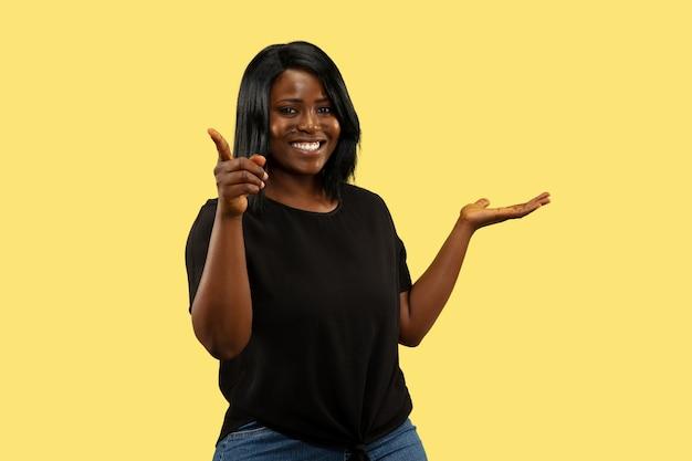 Jeune femme afro-américaine isolée sur l'espace jaune, expression faciale. beau portrait de femme demi-longueur.