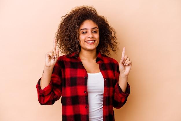 Jeune femme afro-américaine isolée sur fond beige indique avec les deux doigts avant montrant un espace vide.