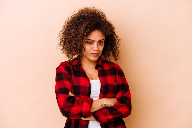 Jeune femme afro-américaine isolée sur fond beige malheureuse à la recherche à huis clos avec une expression sarcastique.