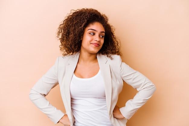 Jeune femme afro-américaine isolée sur fond beige, rêvant d'atteindre les objectifs et les fins