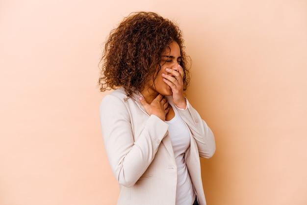 Jeune femme afro-américaine isolée sur fond beige souffre de douleurs dans la gorge en raison d'un virus ou d'une infection.