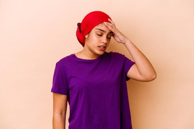 Jeune femme afro-américaine isolée sur fond beige touchant les temples et ayant des maux de tête.