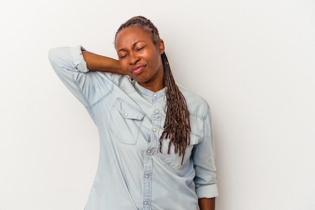 Jeune femme afro-américaine isolée sur fond blanc ayant une douleur au cou due au stress, en la massant et en la touchant avec la main.