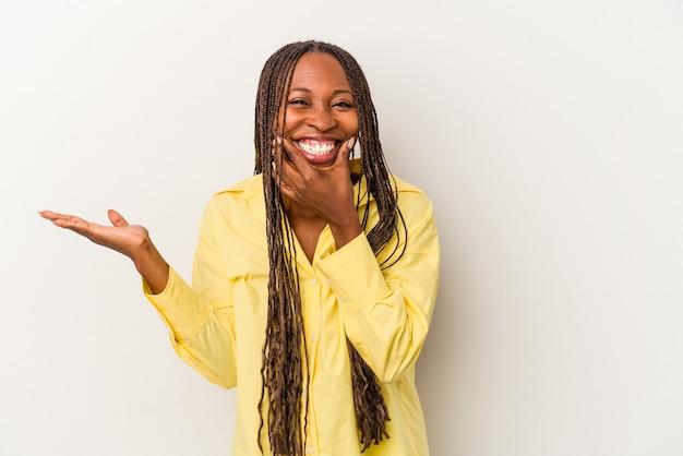 Jeune femme afro-américaine isolée sur fond blanc détient un espace de copie sur une paume, gardez la main sur la joue. émerveillé et ravi.