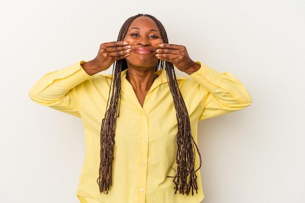 Jeune femme afro-américaine isolée sur fond blanc, doutant entre deux options.