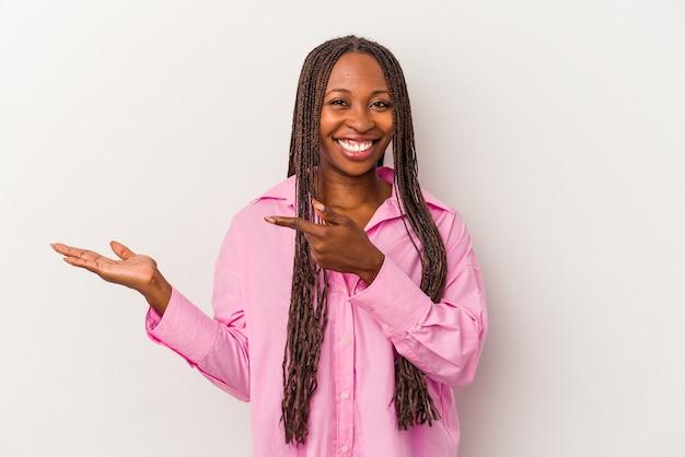 Jeune femme afro-américaine isolée sur fond blanc excitée tenant un espace de copie sur la paume.