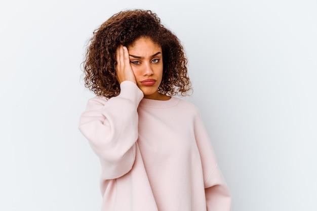 Jeune femme afro-américaine isolée sur fond blanc fatigué et très endormi en gardant la main sur la tête.