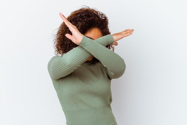 Jeune femme afro-américaine isolée sur fond blanc en gardant deux bras croisés, concept de déni.