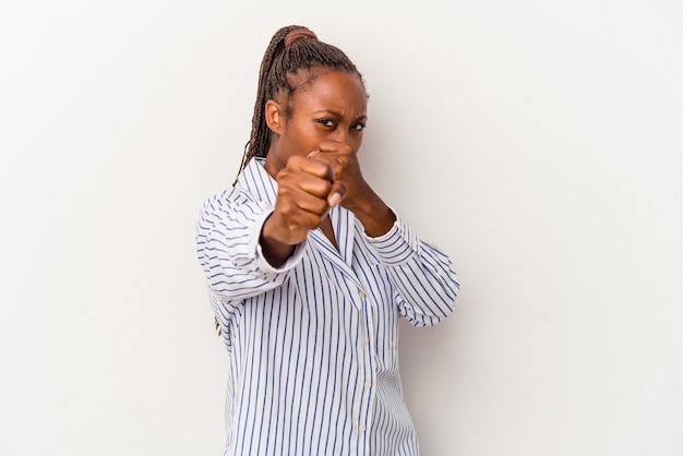 Jeune femme afro-américaine isolée sur fond blanc jetant un coup de poing, colère, combat à cause d'une dispute, boxe.