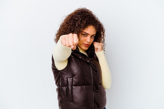 Jeune femme afro-américaine isolée sur fond blanc jetant un coup de poing, la colère, les combats en raison d'une dispute, la boxe.