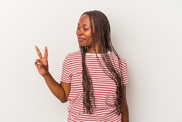 Jeune femme afro-américaine isolée sur fond blanc joyeuse et insouciante montrant un symbole de paix avec les doigts.