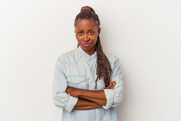 Jeune femme afro-américaine isolée sur fond blanc malheureux à la recherche à huis clos avec une expression sarcastique.