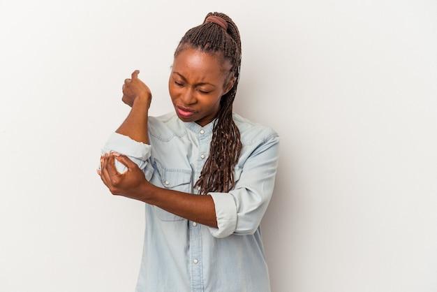 Jeune femme afro-américaine isolée sur fond blanc massant le coude, souffrant après un mauvais mouvement.