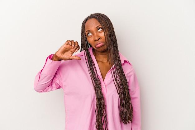 Jeune femme afro-américaine isolée sur fond blanc montrant un geste d'aversion, les pouces vers le bas. notion de désaccord.