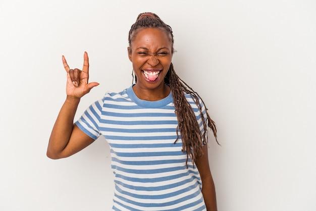 Jeune femme afro-américaine isolée sur fond blanc montrant un geste de cornes comme concept de révolution.