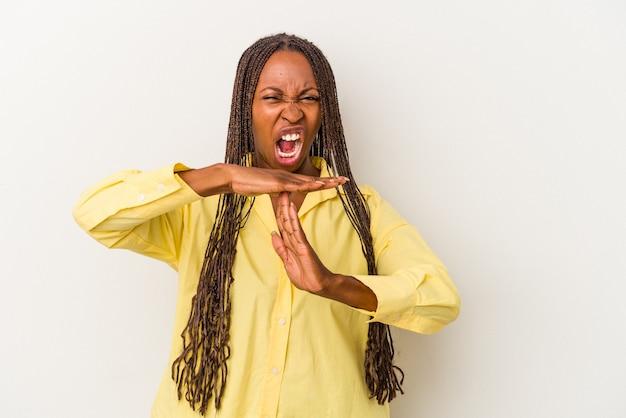 Jeune femme afro-américaine isolée sur fond blanc montrant un geste de délai d'attente.