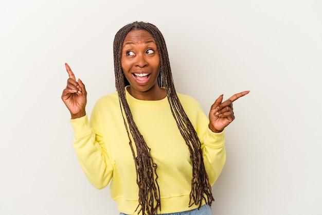 Jeune femme afro-américaine isolée sur fond blanc pointant vers différents espaces de copie, en choisissant l'un d'entre eux, montrant avec le doigt.