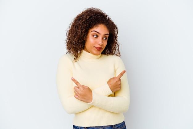 Jeune femme afro-américaine isolée sur fond blanc pointe sur le côté, essaie de choisir entre deux options.