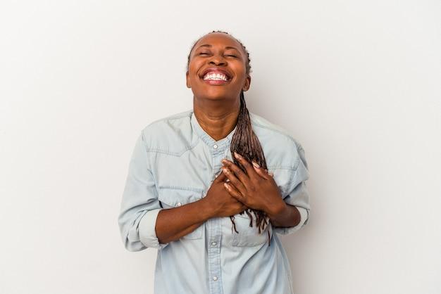 Jeune femme afro-américaine isolée sur fond blanc en riant en gardant les mains sur le cœur, concept de bonheur.