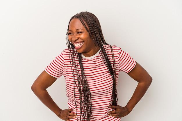 Jeune femme afro-américaine isolée sur fond blanc rit joyeusement et s'amuse en gardant les mains sur le ventre.